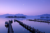 Landing stage and boats at dawn in Gstadt at lake Chiemsee with Fraueninsel, Hochplatte, Hochgern and Hochfelln in the background, Chiemgau, Upper Bavaria, Bavaria, Germany