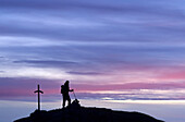Mountaineer at a cross on the summit with pink clouds, Monte Penna, Pelmo range, Dolomites, Venezia, Italy