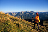 Hiker at Sonntagshorn with view to Berchtesgaden range, Chiemgau alps, Salzburg, Austria