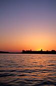 Silhouette von Frauenchiemsee nach Sonnenuntergang gegen den glühenden Abendhimmel, Chiemsee, Chiemgau, Oberbayern, Bayern, Deutschland