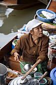 Woman offering food at Floating Market, Damnoen Saduak, near Bangkok, Ratchaburi, Thailand
