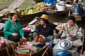 Laughing market-woman holding a dish, another watching her, Floating Market, Damnoen Saduak, near Bangkok, Ratchaburi, Thailand