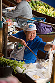 Woman cooking in a boat at Floating Market, Damnoen Saduak, near Bangkok, Ratchaburi, Thailand