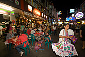 View inside the busy Th Khao San Road with restaurants and street vendors in the evening, Banglamphu, Bangkok, Thailand