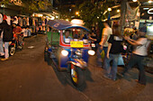 Tuk Tuk passing Th Khao San Road in the evening, Banglamphu, Bangkok, Thailand
