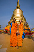 Two monks in front of gilded Chedi, housed a Buddha relic of the Wat Saket on the Golden Mount, Bangkok, Thailand
