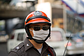 Policeman protecting against air pollution, Sukhumvit Road, Bangkok, Thailand