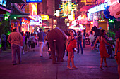 People strolling over Soi Cowboy with bars and nightclubs, red-light district, woman smiling at camera in foreground, Th Sukhumvit, Bangkok, Thailand