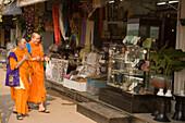 Two buddhist monks walking over the Suan Chatuchak Weekend Market, Bangkok, Thailand