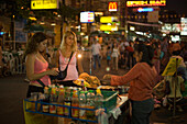 People standing around a food stand at Th Khao San Road in the evening, Banglamphu, Bangkok, Thailand
