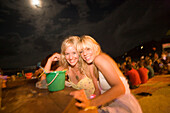 Two girls drinking out of a small green pail, Full Moon Party, Hat Rin Nok, Sunrise Beach, Ko Pha-Ngan, Thailand