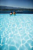 Couple enjoying the view from a pool overlooking the bay of Porto Vecchio, Southern  Corse, France