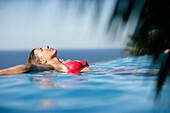 Woman in bikini leaning back in infinity pool, Porto Vecchio, Southern Corse