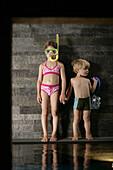 Girl  wearing diving googles, holding brother's hand, Hotel Krallerhof, Leogang, Salzburger Land, Austria