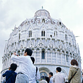 Asian tourists in front of the baptistry at Pisa, Tuscany, Italy