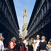 People standing in a queue in front of Uffizi, Palazzo Vecchio in the background, Firence, Italy