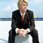 Young blond businessman sitting on square