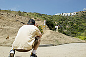 Tourists posing in front of the Hollywood sign, tourists taking picture, emblem, Los Angeles, L.A., Caifornia, U.S.A., United States of America