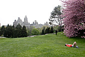 Jogger relaxes on lawn , Spring, Upper East Side, Manhattan, New York City, New York, United States of America, U.S.A.