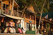Girls sitting in front of a clothes shop at boardwalk, Ko Phi Phi Don, Ko Phi Phi Island, Krabi, Thailand, after the tsunami