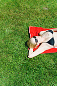 Young woman lying on grass, listening to MP3 player, Starnberger See, Upper Bavaria, Germany