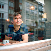 Man sitting in a coffe bar, looking out of the window, Germany