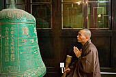Monk in prayer, meditation, bronze bell, Wannian Monastery and Temple, China