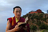 Tibetan monk reading holy scripts at sunrise, Emei Shan mountains, Sichuan province, China, Asia