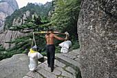 porter carrys building material on his back up steep mountain steps, Taoist mountain, Hua Shan, Shaanxi province, Taoist mountain, China, Asia