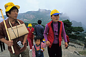 Tourist group, family with yellow caps, view from peak, Huang Shan, Anhui province, World Heritage, UNESCO, China, Asia