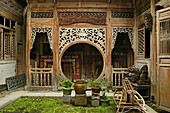 courtyard with elaborate carved timber screens, pot plants, Hongcun, ancient village, living museum, China, Asia, World Heritage Site, UNESCO
