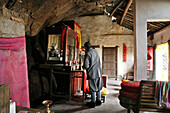 A monk standing in front of the altar of a cave temple, Jiuhuashan, Anhui province, China, Asia