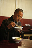 monk with bowl of rice, dining room, Longevity Monastery, Jiuhuashan, Mount Jiuhua, mountain of nine flowers, Jiuhua Shan, Anhui province, China, Asia
