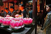 Pilgrims lighting up candles in the form of lotus flowers, Longevity monastery, Jiuhua Shan, Anhui province, China, Asia