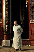Mature monk standing in front of Avalokiteshvara monastery in the sunlight, Jiuhua Shan, Anhui province, China, Asia
