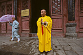 Shaolin monk leaving the temple after prayer, Shaolin Monastery, known for Shaolin boxing, Taoist Buddhist mountain, Song Shan, Henan province, China