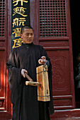 Buddhist Shaolin monk striking a wooden gong, Call for prayer, Shaolin Monastery, known for Shaolin boxing, Taoist Buddhist mountain, Song Shan, Henan province, China