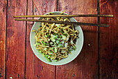 Chinese food, bowl of noodles with chilli, spring onions and sugar on a red tablespringonions, typical street snack in Sichuan, China