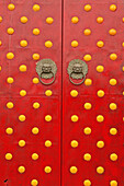 temple door, gate, double doors in red with round yellow decorations, lion door knockers, China, Asia