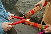 lighting bundles of incense sticks with red candles, pilgrims, China, Asien