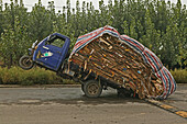 Overloaded three-wheeler on a deserted road, China, Asia