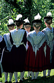 Group of young women in dirndl dresses from the back with traditional hats and eagle down feathers, pilgrimage to Raiten, Schleching, Chiemgau, Upper Bavaria, Bavaria, Germany