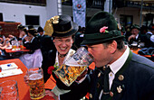 Young couple in dirndl dress and traditional dress, saying cheers in a beer garden, pilgrimage to Raiten, Schleching, Chiemgau, Upper Bavaria, Bavaria, Germany