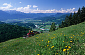 Two hikers sitting on a bench at Kranzhorn with a view over the Inn valley, Kaiser Mountain Range and Central Eastern Alps, Chiemgau Alps, Tyrol, Austria