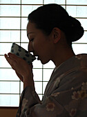 Japanese woman drinking tea, tea ceremony in Hosomi museum, Kyoto, Japan
