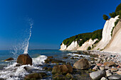 Waves splashing against rocks with chalk cliffs in the background, Jasmund National Park, Mecklenburg Western Pomerania, Germany