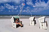 Young woman in beach chair, Wangerooge, North Sea, Germany