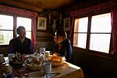 Couple eating breakfast in an alpine hut, Pleissen Hut, Scharnitz, Austria