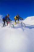 Two mountain bikers riding through deep snow, Serfaus, Tyrol, Austria