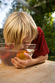 Boy teating an apple in a dish with water, children's birthday party